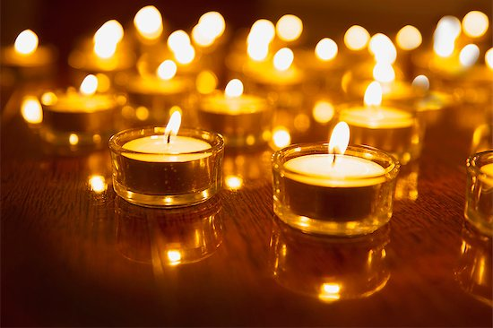619-07558828 © Masterfile Royalty-Free Model Release: No Property Release: No Close up of lit tea light candles on wooden table